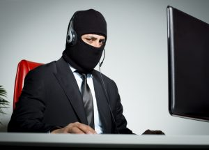 Anonymous man with mask using computer